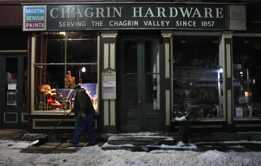 Rob Schwind shovels the sidewalk in front of the Chagrin Hardware in Chagrin Falls, Ohio.