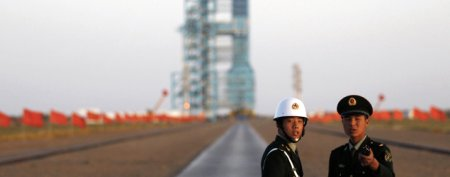 Reuters/Reuters - Soldiers stand in front of the Long March II-F rocket loaded with China's unmanned space module Tiangong-1 before its planned launch from the Jiuquan Satellite Launch Center, Gansu province in this September 29, 2011 file photo. REUTERS/Petar Kujundzic/Files