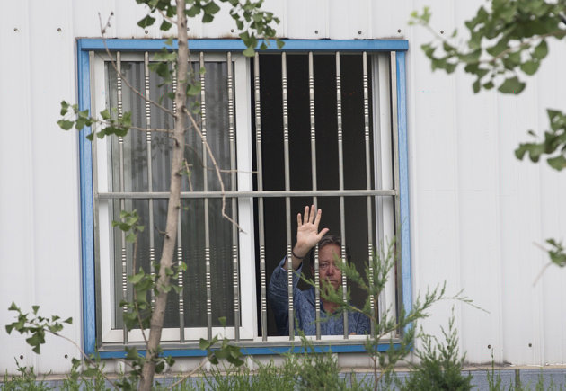 Associated Press/Andy Wong - American Chip Starnes, co-owner of Specialty Medical Supplies, waves from a window after he was held hostage by workers inside his plant at the Jinyurui Science and Technology Park in Qiao Zi township of Huairou District, on the outskirts of Beijing, China Monday, June 24, 2013. An American executive said Monday Starnes has been held hostage for four days at his medical supply plant in Beijing by dozens of workers demanding severance packages like those given to co-workers in a phased-out department. (AP Photo/Andy Wong)